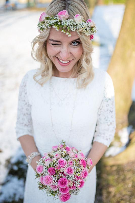 Braut auf einer Winterhochzeit die einen Hochzeitsstrauß in den Händen hält