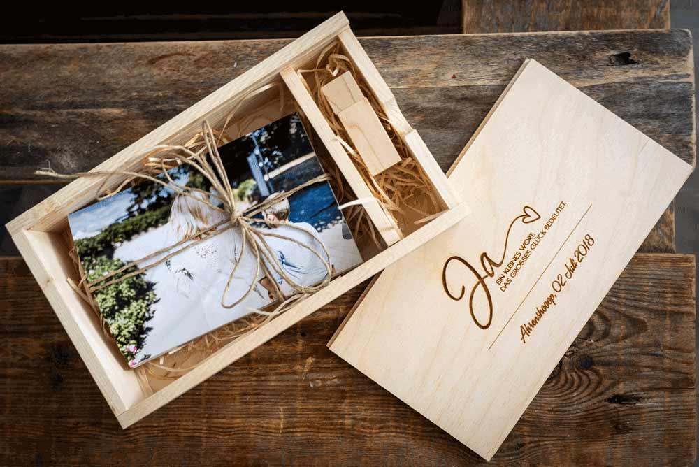 Eine Box aus Holz wo gedruckte Bilder von einer Hochzeits drin sind. Ebenso befindet sich ein USB Stick darin.